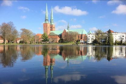 Im Vordergrund ist der Mühlenteich zu sehen, in welchen sich der der Dom spiegelt. Der Dom ist im Hintergrund zu sehen. Die Türme ragen in den nur leicht mit wolken bedeckten Himmel - Copyright: Ev.-Luth. Kirchenkreis Lübeck-Lauenburg