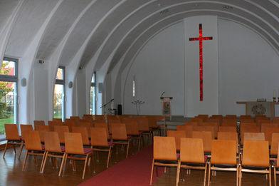 Stuhlreihen auf rotem Teppich / an der vorderen weißen Wand ist ein rotes Kreuz aus Glas zu sehen - Copyright: Ev.-meth. Kirche