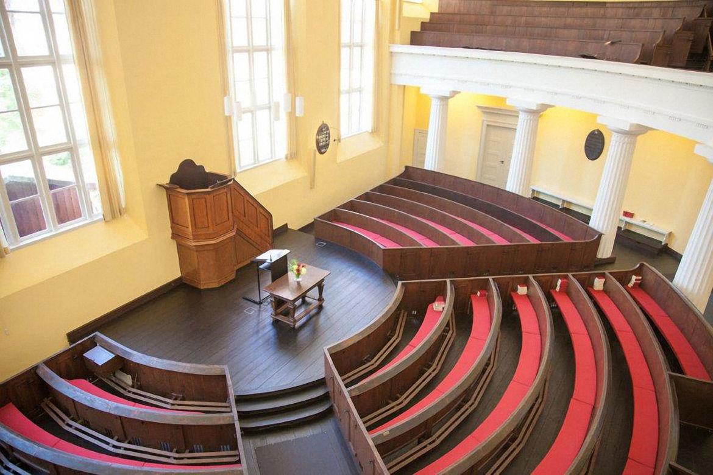 Leere Bankreihen in einem Halbkreis um eine Kanzel herum / große Fenster mit weißen Holzrahmen und eine Empore mit Holzbänken ist zu sehen - Copyright: Reformierte Kirche Lübeck