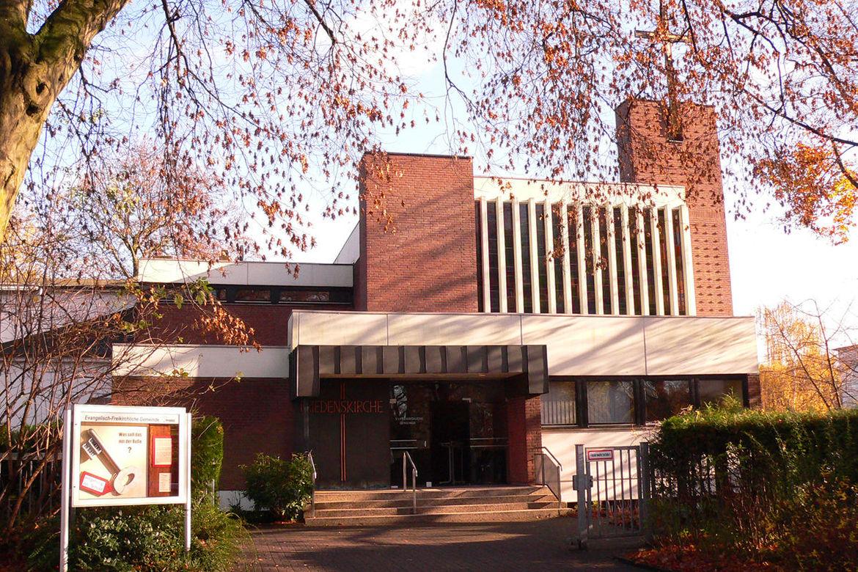 Der Eingangsbereich der Friedenskirche ist zu sehen. Links im Vordergrund steht ein Schaukasten.  - Copyright: Volkmar Glöckner